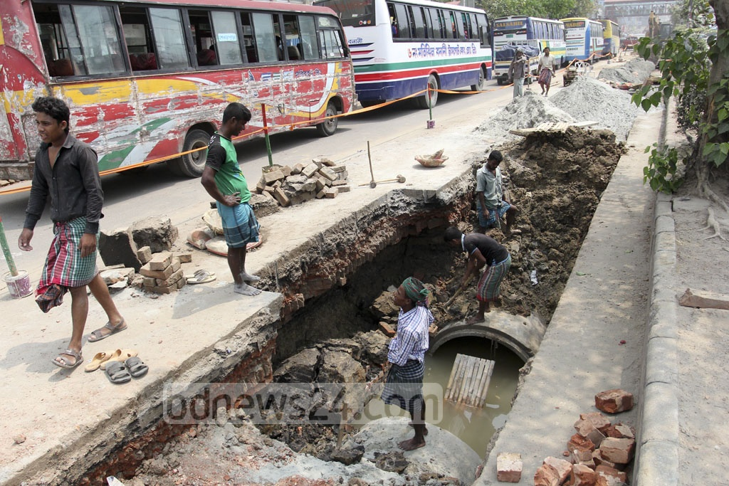 Labourers lay down sewage pipes in Dhaka's Pragati Sarani on Saturday. Photo: asif mahmud ove