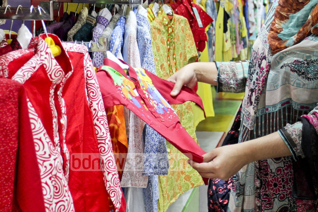 A customer is checking a dress for her child at a shop ahead of the Pahela Baishakh.