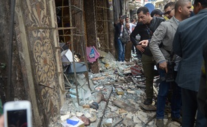 Egyptians look at victims after suicide blast in front of church in Alexandria.