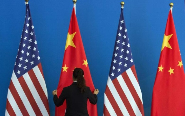 A Chinese woman adjusts a Chinese national flag next to US national flags before a Strategic Dialogue expanded meeting, part of the US-China Strategic and Economic Dialogue (S&ED) held at the Diaoyutai State Guesthouse in Beijing, Jul 10, 2014. Reuters