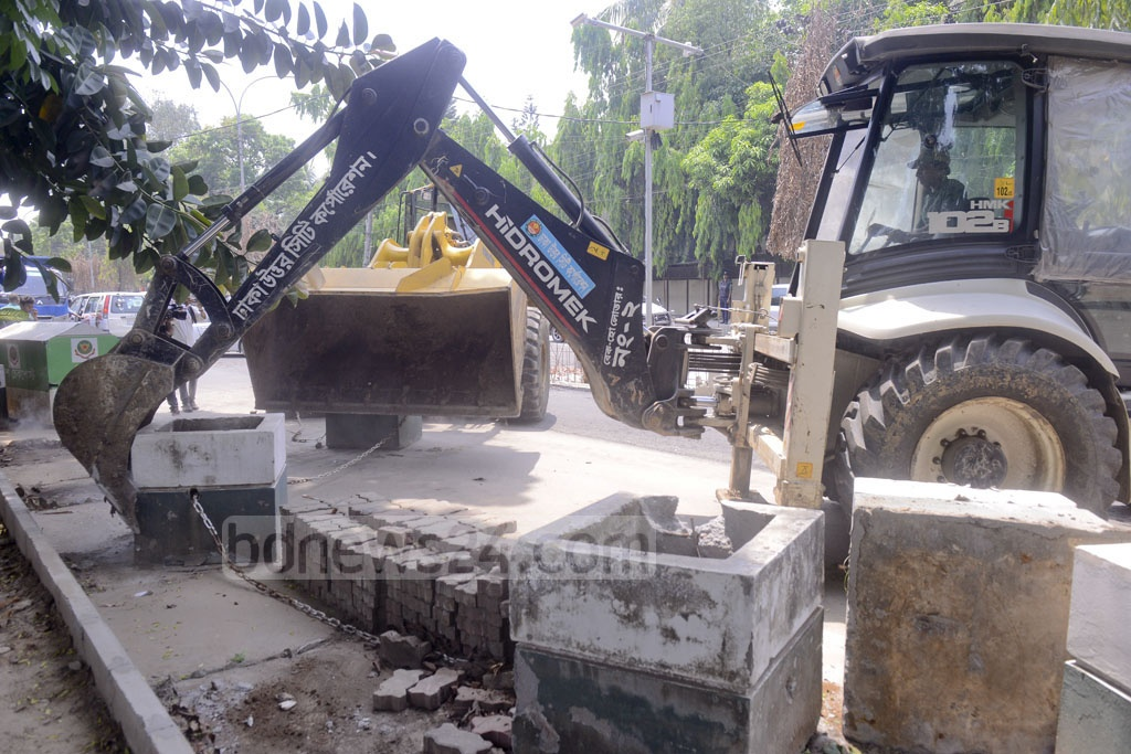 Dhaka North City Corporation clears a 400-foot sidewalk occupied by concrete blocks and fences belonging to the Pakistan High Commission, widening the road for traffic in Gulshan on Tuesday.