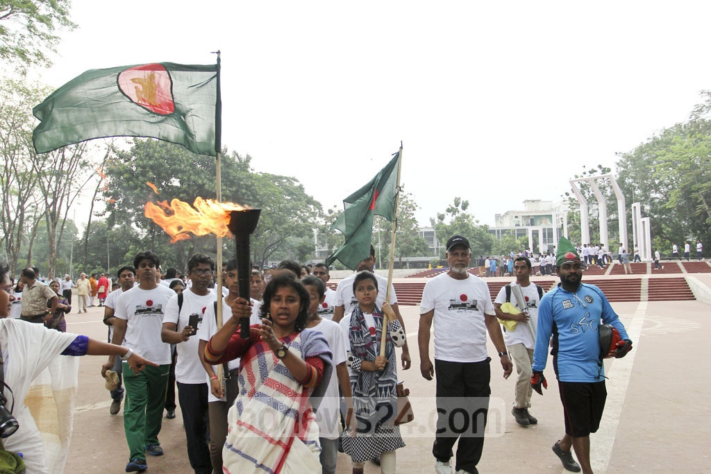 A 71-member torch bearing team carries an eternal flame from the old Liberation War Museum building in Segunbagicha to the Central Shaheed Minar and then to Suhrawardy Udyan on Saturday. Photo: asif mahmud ove