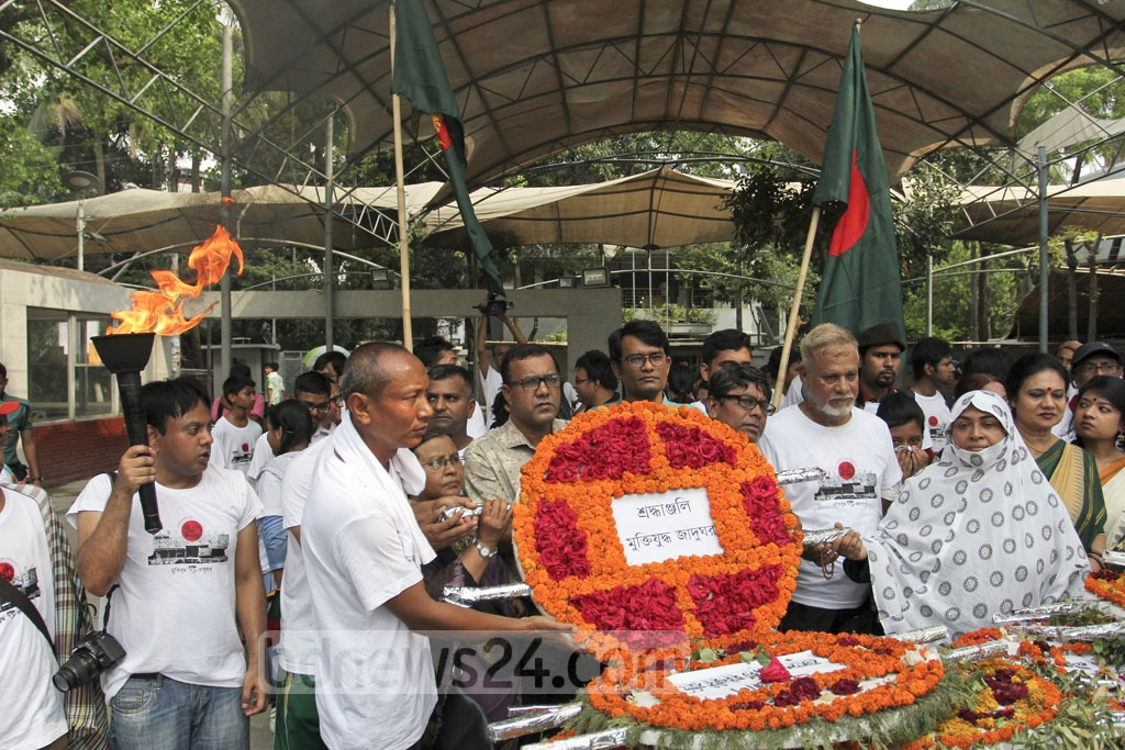 Families of Liberation War martyrs pay tributes to the eternal flame in front of the Bangabandhu Museum in Dhanmondi on Saturday. Photo: asif mahmud ove