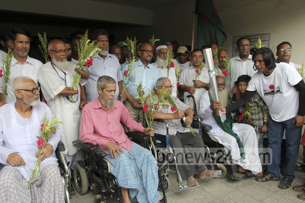 A team of torch bearers presents flowers to freedom fighters wounded in the Liberation War at Freedom Fighter Tower in Mohammadpur on Saturday. Photo: asif mahmud ove
