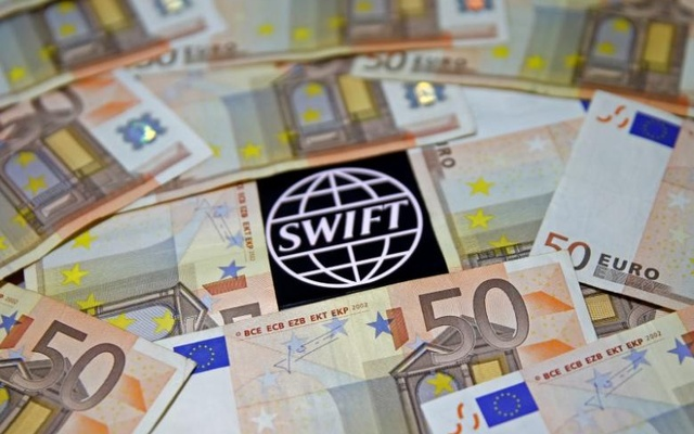 FILE PHOTO: Swift code bank logo is displayed on an iPhone 6s among Euro banknotes in this picture illustration January 26, 2016. Reuters