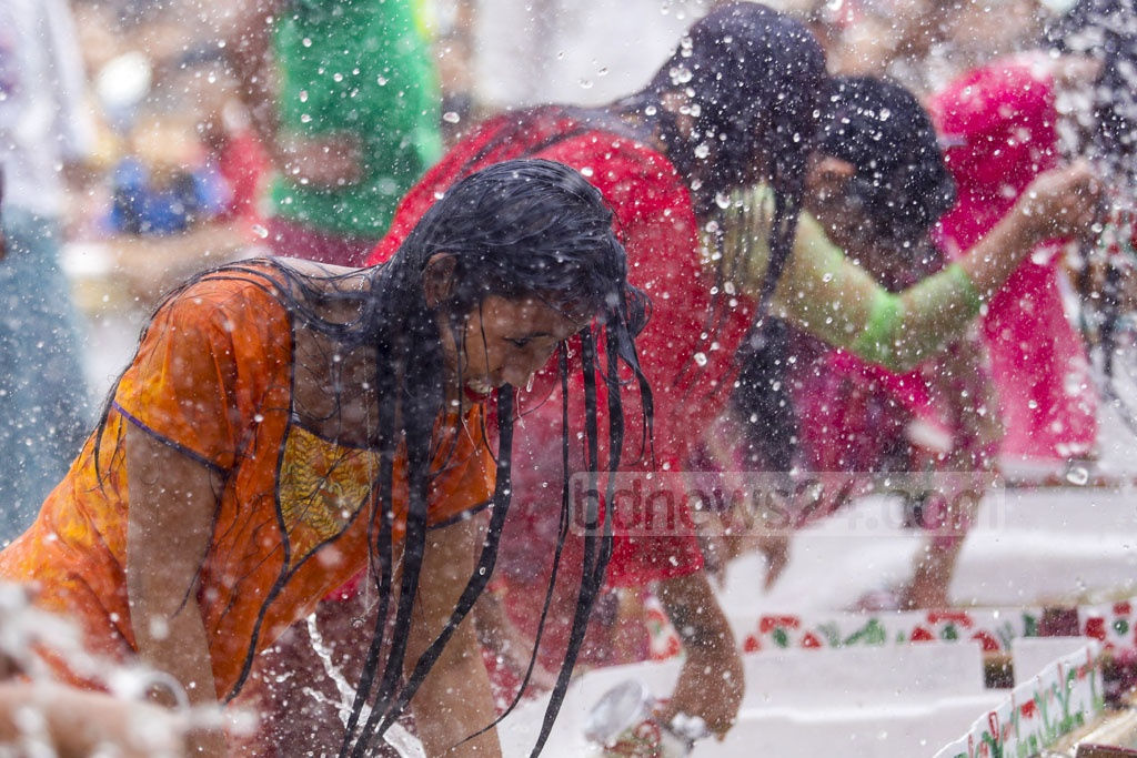 ​Marma tribal girls are splashing water as part of the Sangrai water festival organised to celebrate the new year at Betbunia High School at Kawkhali​ Upazila in Rangamati on Sunday. Photo: mostafigur rahman