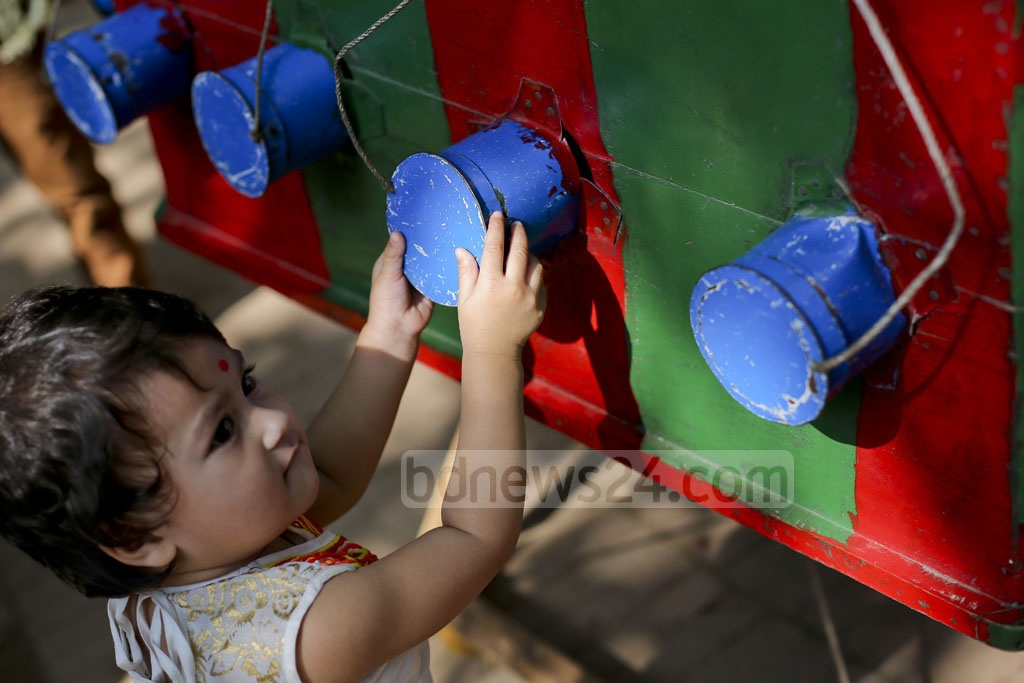 A child looks at the old projector, painted red and green, like Bangladesh's flag. Photo: asaduzzaman pramanik