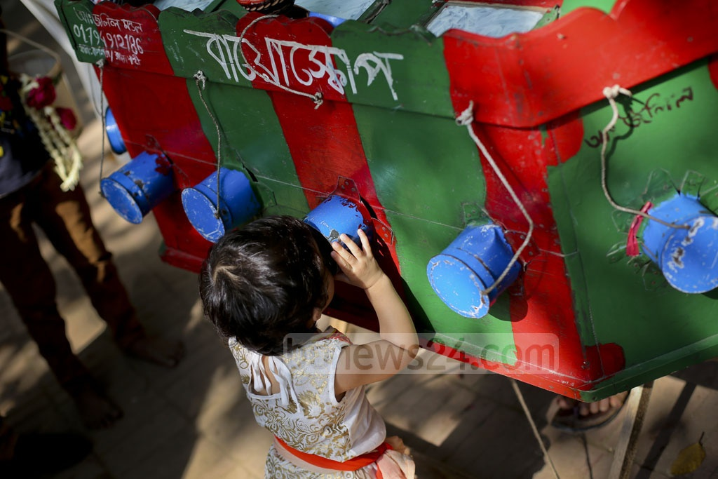 A child peeps through a tinned scope for a look inside the crude projector. Photo: asaduzzaman pramanik