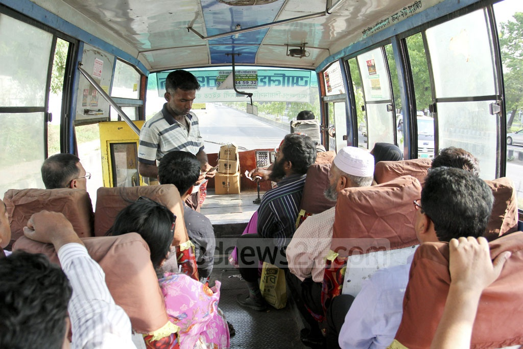 A worker of Alif Paribahan collects fares from passengers on Monday, a day after authorities began shutting down costlier bus services that carried only seated passengers. Photo: asif mahmud ove