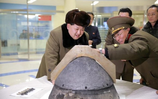 North Korean leader Kim Jong Un looks at a rocket warhead tip after a simulated test of atmospheric re-entry of a ballistic missile, at an unidentified location in this undated photo released by North Korea's Korean Central News Agency (KCNA) in Pyongyang on March 15, 2016. REUTERS/KCNA