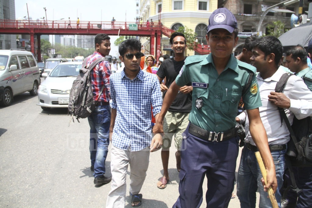 A pedestrian detained by police for jaywalking instead of using the overhead footbridge at the Bangla Motor intersection in Dhaka on Tuesday. Photo: abdul mannan