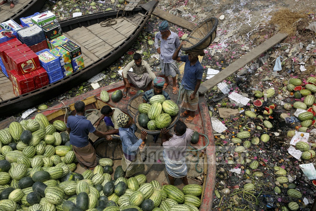 Labourers unload watermelons at Badamtali terminal. They are sold to warehouses between Tk 60 and Tk 370, while the bad ones are dumped into the river. Photo: mostafigur rahman