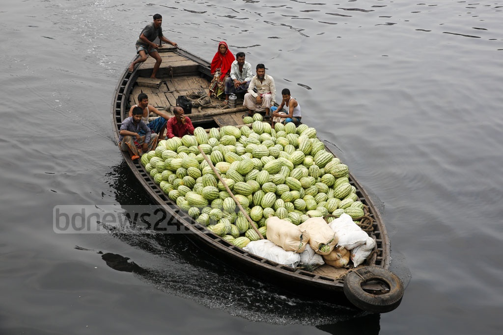 A launch carried these fruits over rivers to Dhaka. They were loaded on this smaller boat now headed to warehouses at Badamtali. Photo: mostafigur rahman