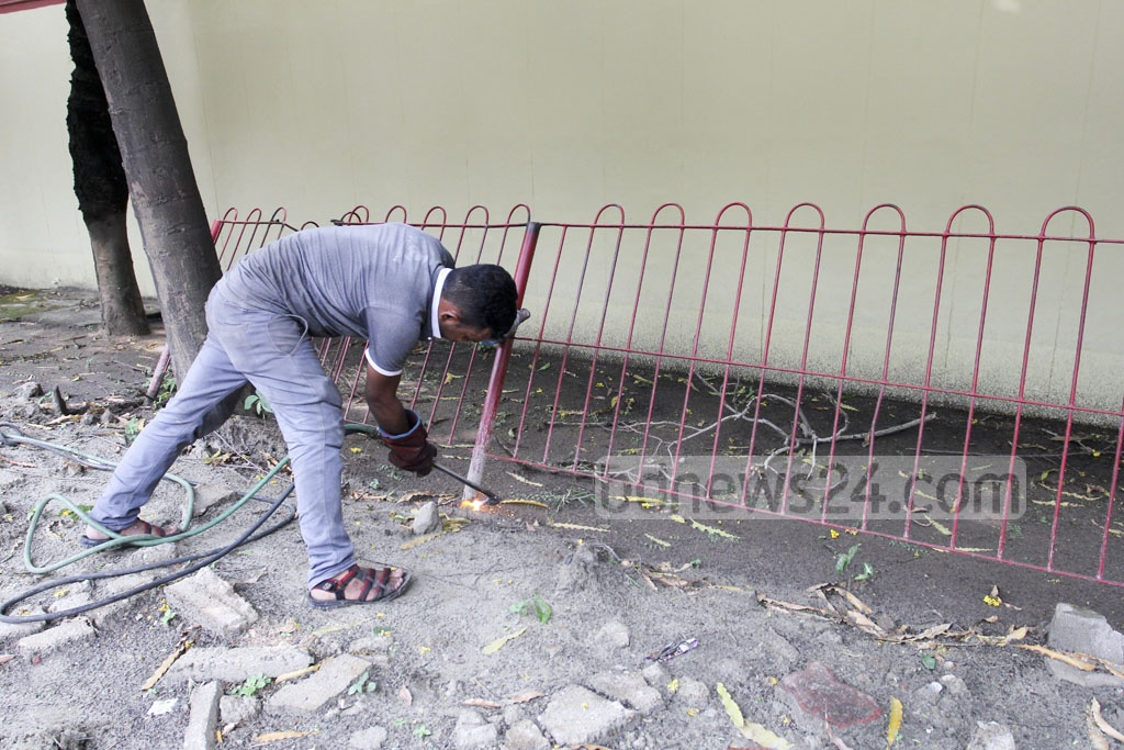 A Dhaka North City Corporation worker removes Russian embassy security fences in Gulshan on Thursday. Photo: asif mahmud ove