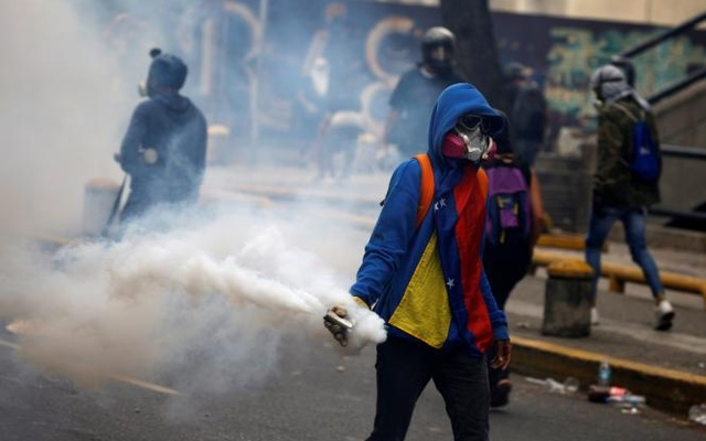 An opposition demonstrator carries a gas grenade while clashing with riot police during the so called 'mother of all marches' against Venezuela's President Nicolas Maduro in Caracas, Venezuela, Apr 19, 2017. Reuters