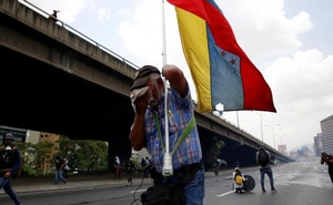 A demonstrator carries Venezuela's flag while clashing with riot police during the so-called 'mother of all marches' against Venezuela's President Nicolas Maduro in Caracas, Venezuela Apr 19, 2017. Reuters