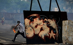 An opposition demonstrator throws a petrol bomb while clashing with riot police during the so called 'mother of all marches' against Venezuela's President Nicolas Maduro in Caracas, Venezuela, Apr 19, 2017. Reuters