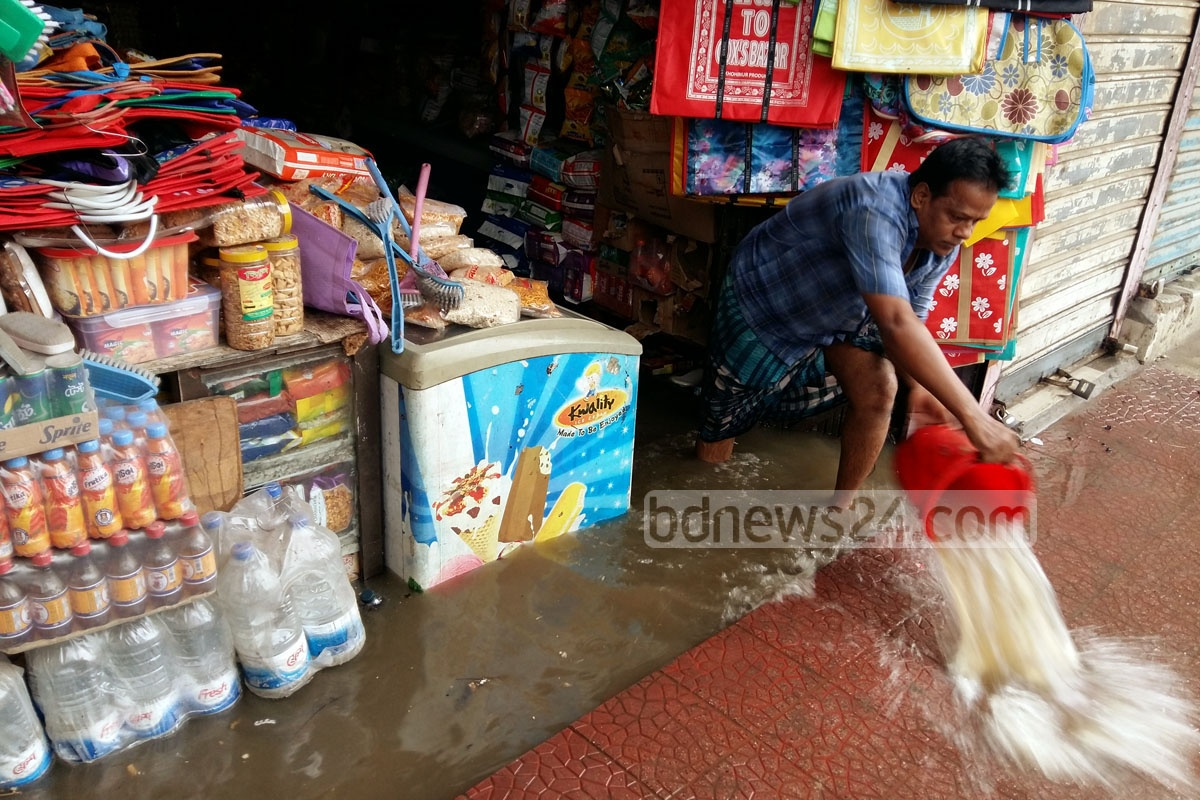 A shopkeeper tries to drain out the water from his shop with a pot in Chittagong City on Friday. Photo: suman babu