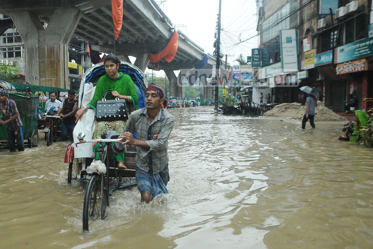 Commuters, who were in trouble due to water-clogged streets in Chittagong on Friday, rely on rickshaw-van as the only transport. Photo: suman babu