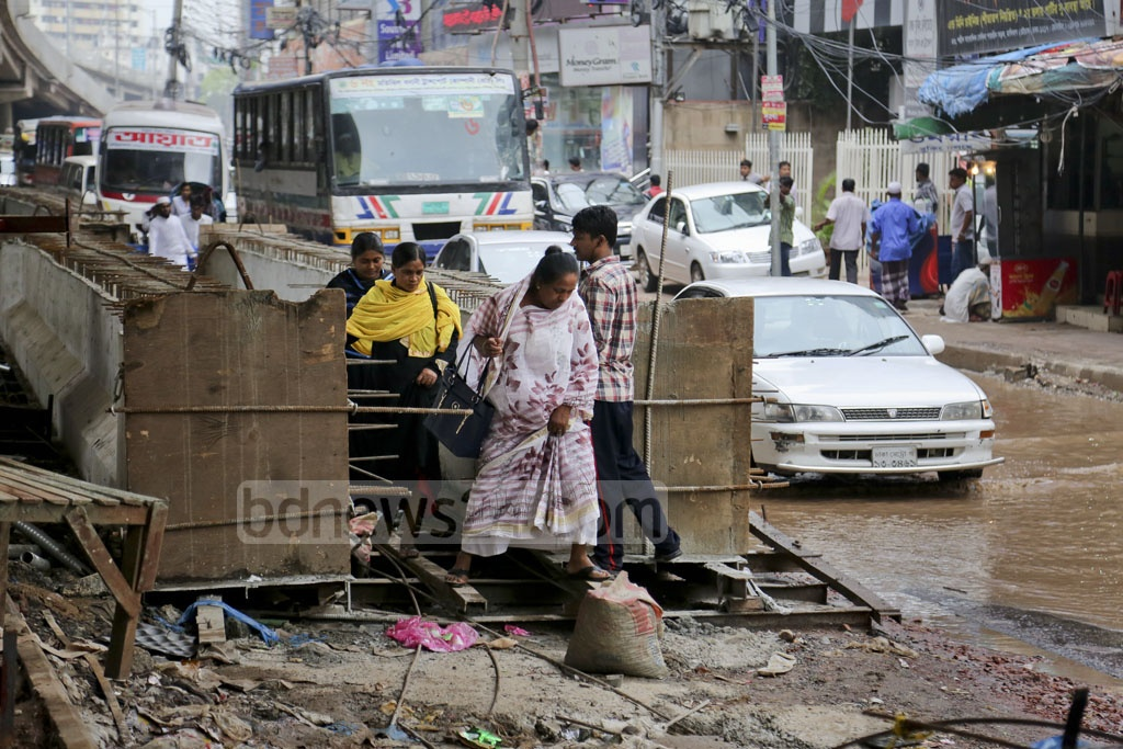 Pedestrians face particular difficulties at the road leading to Mogbazar from the Mouchak intersection due to the combination flooding, illegal parking on the sidewalk and construction work on the flyover. Photo: asaduzzaman pramanik