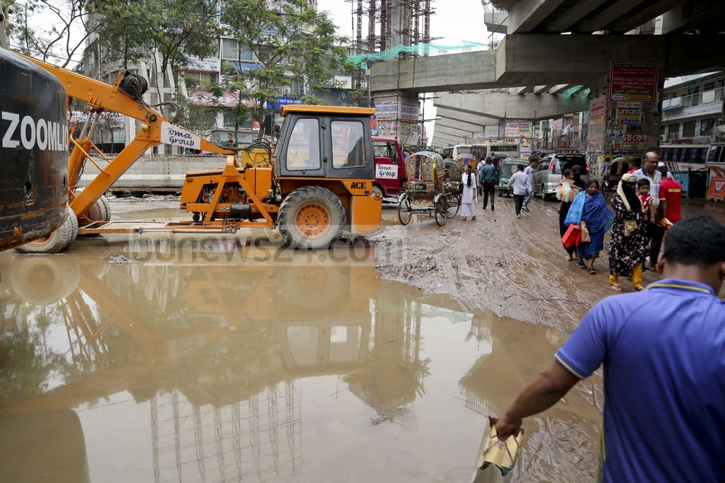 Pedestrians try to navigate waterlogged streets through mud and construction equipment from the Malibagh intersection towards Mouchak on Sunday afternoon. Photo: asaduzzaman pramanik