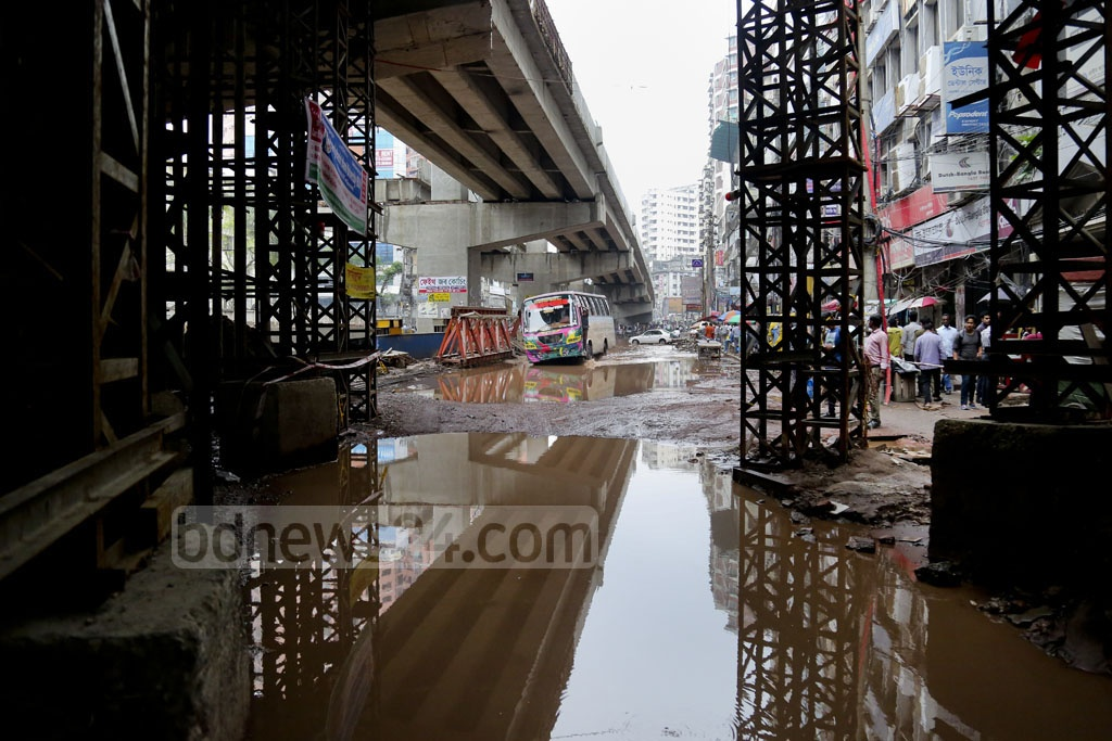 Pedestrians try to navigate the flooded roads and the haphazardly left construction equipment and materials at Dhaka's Malibagh intersection on Sunday afternoon. Photo: asaduzzaman pramanik
