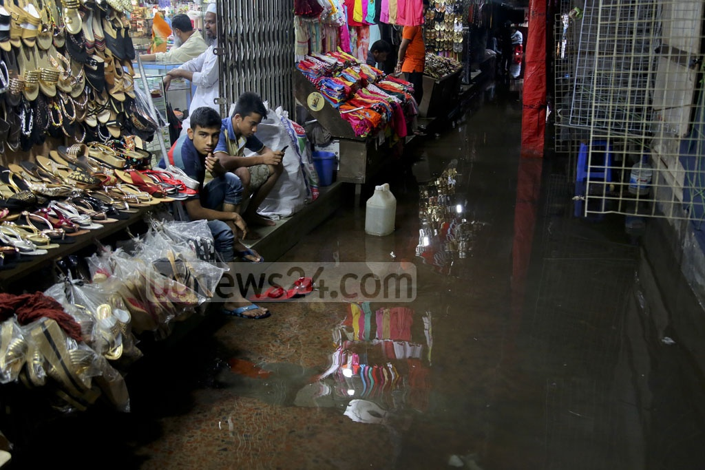 Store workers sit idle as flooding and heavy rains keep customers away from Dhaka's Mouchak market. Photo: asaduzzaman pramanik