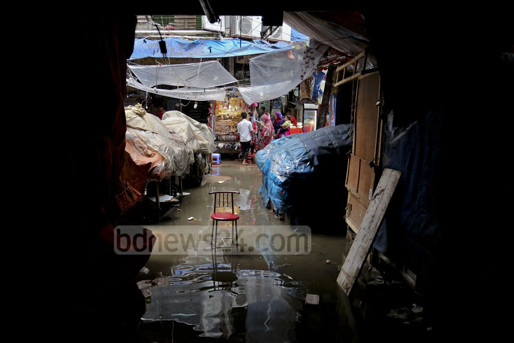 Though stores line both sides of this alley by Dhaka's Mouchak market, heavy rains in the past few days have forced a majority of stores to remain closed. Photo: asaduzzaman pramanik