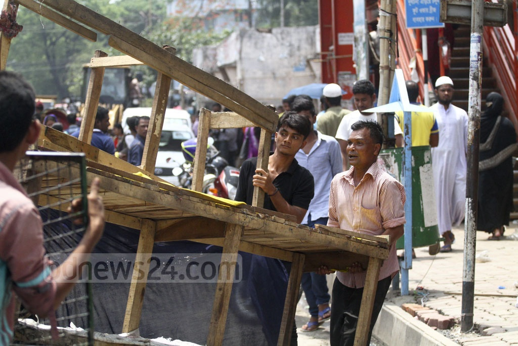 Following ​the eviction by the DSCC, hawkers take their belongings from the footpaths at New Market. Photo: abdul mannan