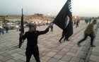 FILE PHOTO: A fighter of the Islamic State of Iraq and the Levant (ISIL) holds an ISIL flag and a weapon on a street in the city of Mosul, June 23, 2014. Reuters