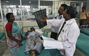 Doctors examine a magnetic resonance imaging (MRI) scan of a patient lying on a bed inside a ward at Rajiv Gandhi Government General Hospital (RGGGH) in Chennai July 12, 2012. Reuters
