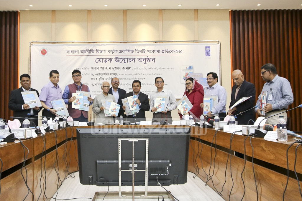 Planning Minister AHM Mustafa Kamal unveils covers of three books launched by the General Economics Division at NEC Seminar Hall in Dhaka's Sher-e-Bangla Nagar on Thursday. Photo: asif mahmud ove