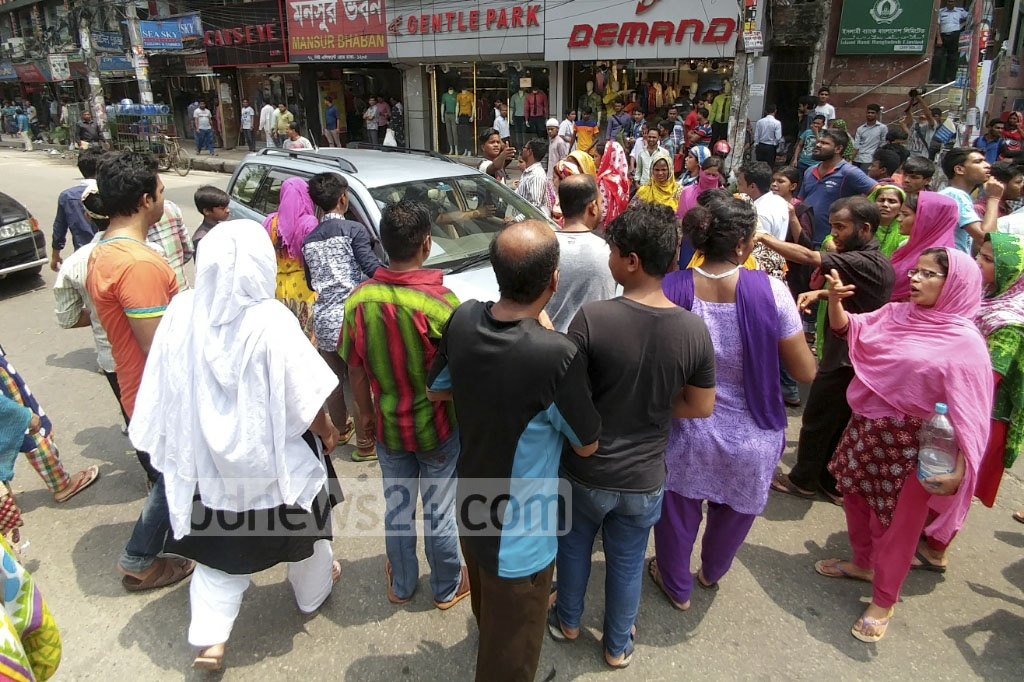 Agitating workers block the road in front of Multiplan Centre at Dhaka's Elephant Road in protest against a 'sudden closure' of Hexa Garments Ltd owned by Alif Group on Thursday. Photo: abdul mannan