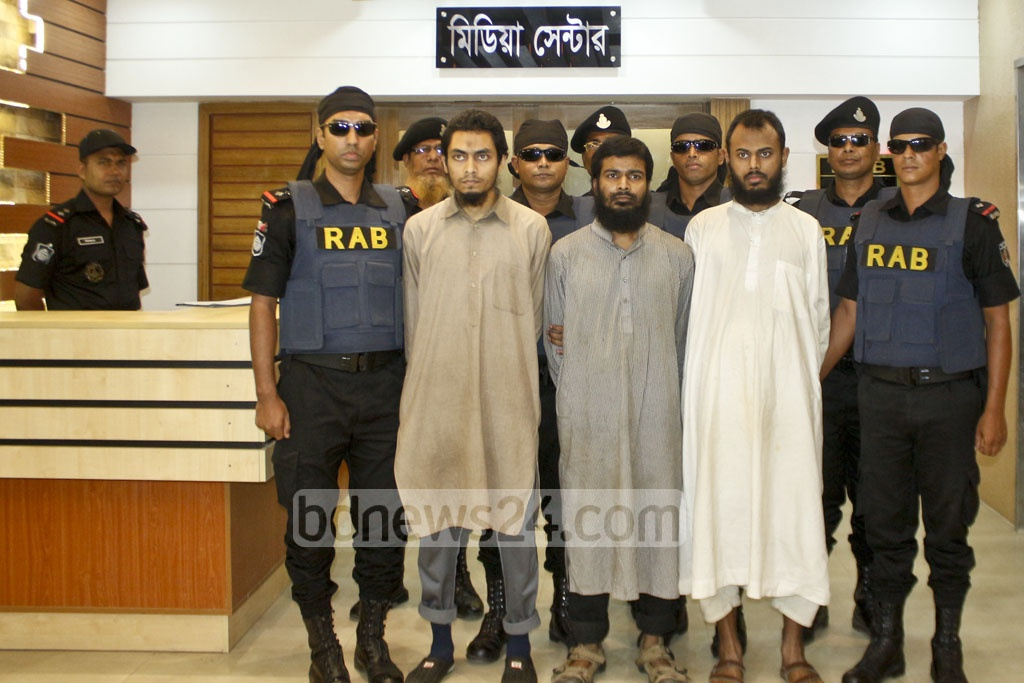 Three suspected militants are brought to a press briefing by the Rapid Action Battalion on Friday following their arrest from a bus in Savar.