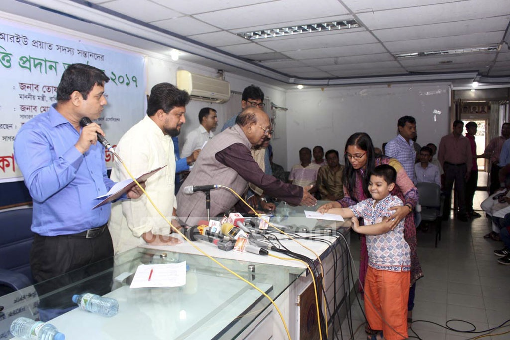 Commerce Minister Tofail Ahmed hands scholarship cheques to children of deceased journalists at Dhaka Reporters' Unity on Friday.