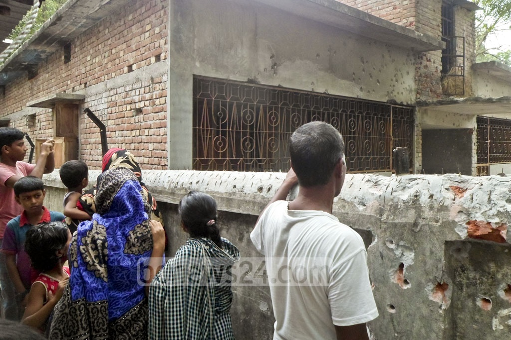 A curious crowd gathers to look at bullet holes in the wall near the alleged militant hideout in Chapainawabganj's Shibhanj after the SWAT raid.