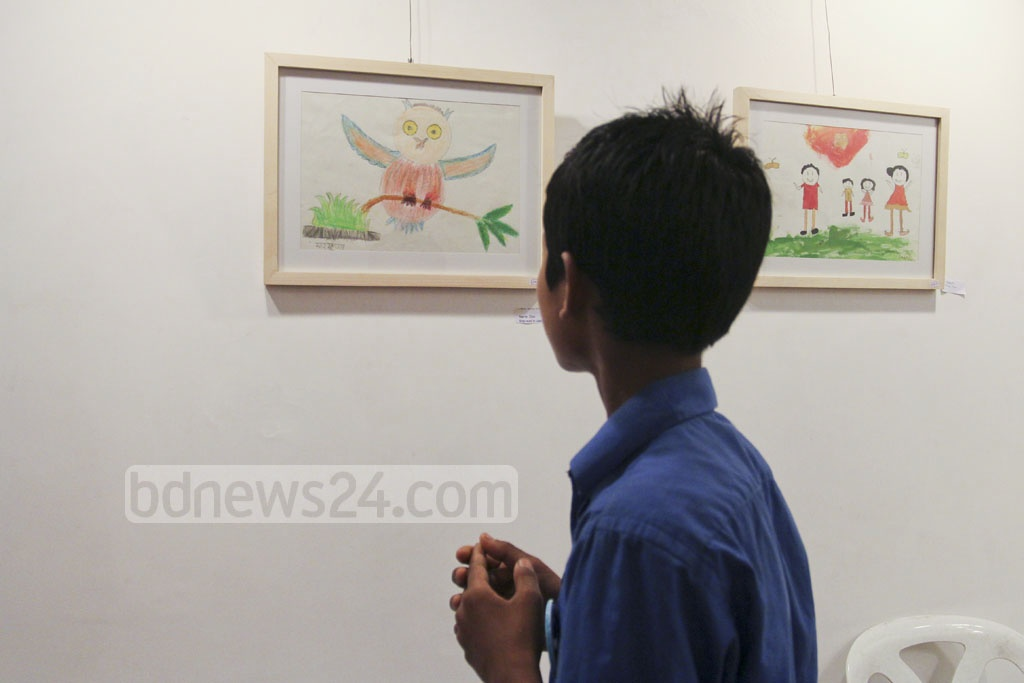 A child looks at a drawing during an exhibition of art by underprivileged children at Dhaka's Drik Gallery on Saturday. Photo: asif mahmud ove