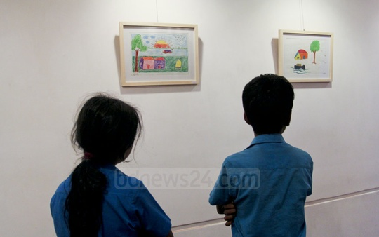 Children look at drawings by underprivileged children during an exhibition at Dhaka's Drik Gallery on Saturday. Photo: asif mahmud ove