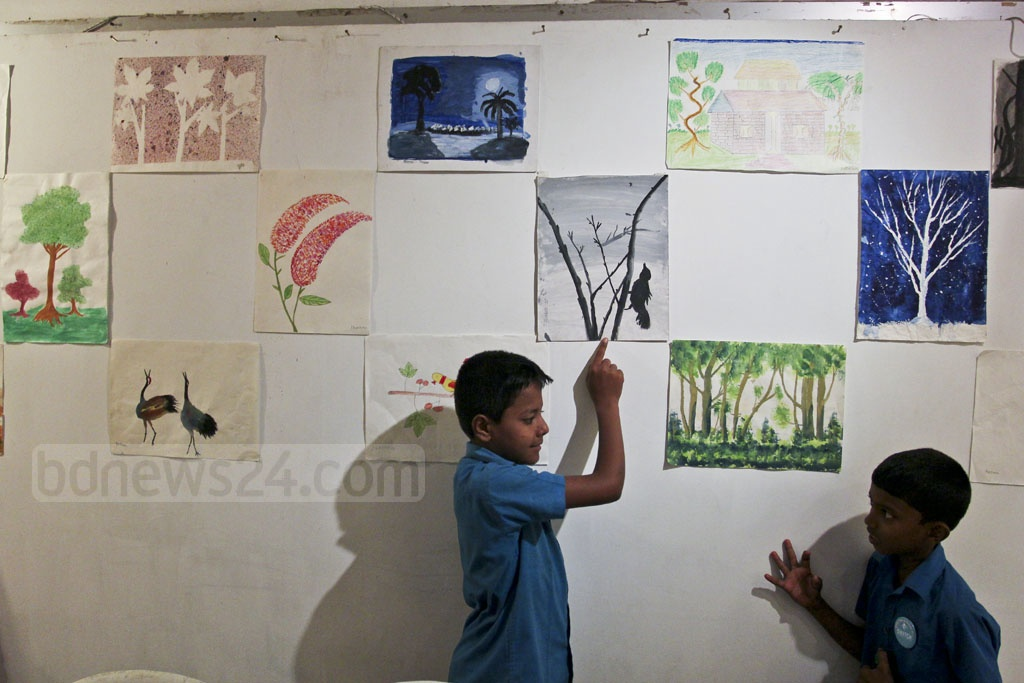 A child points out his painting at an exhibition of art by underprivileged children at Dhaka's Drik Gallery on Saturday. Photo: asif mahmud ove