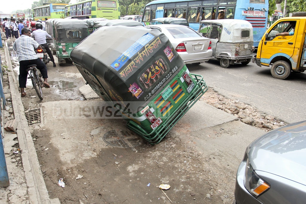 An autorickshaw is stuck in a hole caused by unfinished road construction near Rapa Plaza on Dhaka's Mirpur Road. Photo: asif mahmud ove