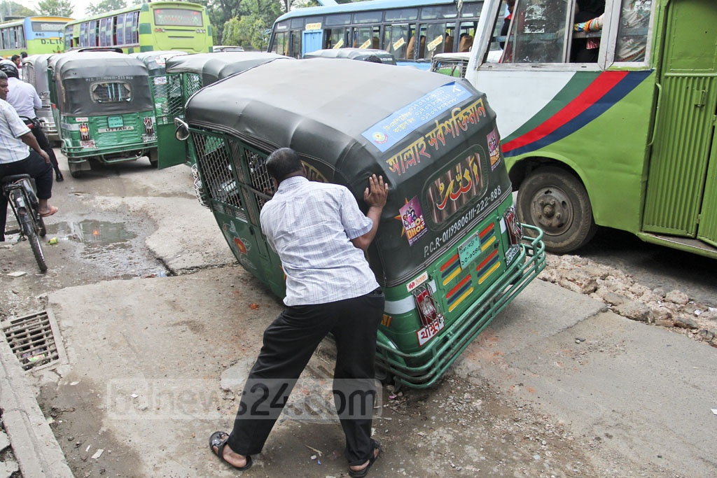 A man tries to push an autorickshaw out of a hole caused by unfinished road construction near Rapa Plaza on Dhaka's Mirpur Road. Photo: asif mahmud ove