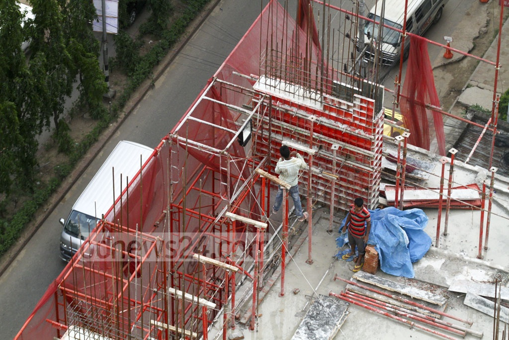 Construction workers are seen without safety equipment at a high-rise building in Dhaka. Photo: abdul mannan