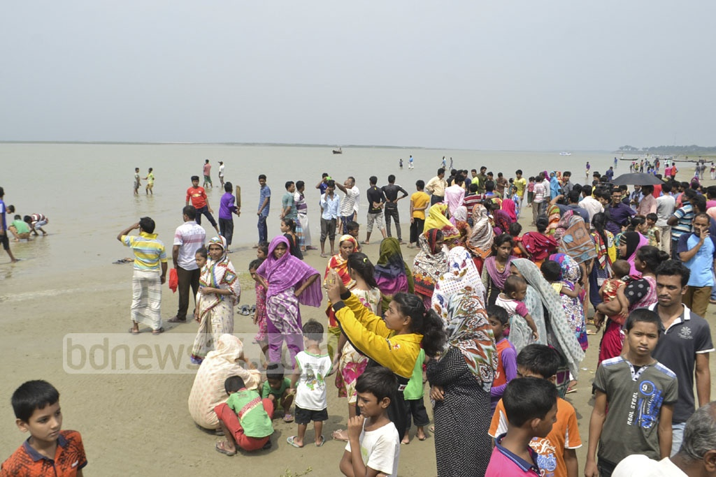 Relatives of four people, who went missing in a boat capsize during a storm, wait on the bank of the Padma river in Rajshahi on Monday as search operation continues. The nor'wester has caused havoc and claimed lives in the district. Photo: Gulbar Ali Juwel