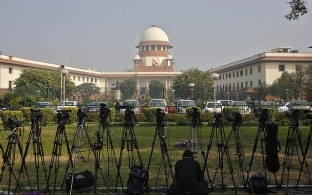 This 2014 photos shows a television journalist sets his camera inside the premises of the Supreme Court in New Delhi, India. Reuters