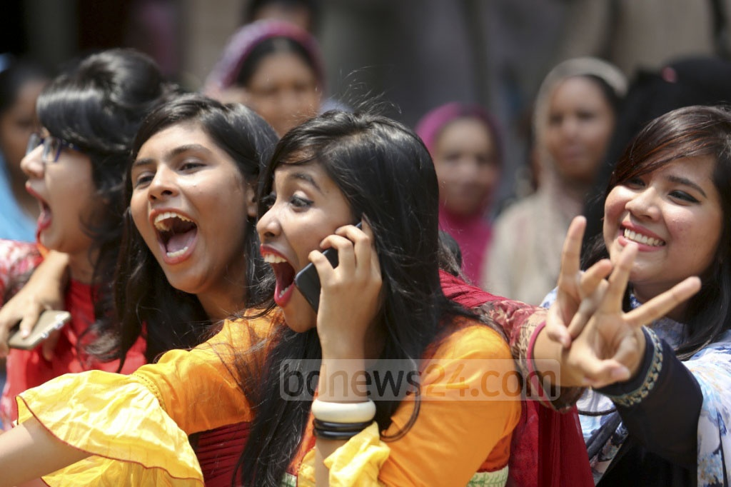 A student of Dhaka's Motijheel Ideal School shares her joy on mobile phone after doing well in the SSC exams. The photo was taken from her school premises. Photo: asaduzzaman pramanik