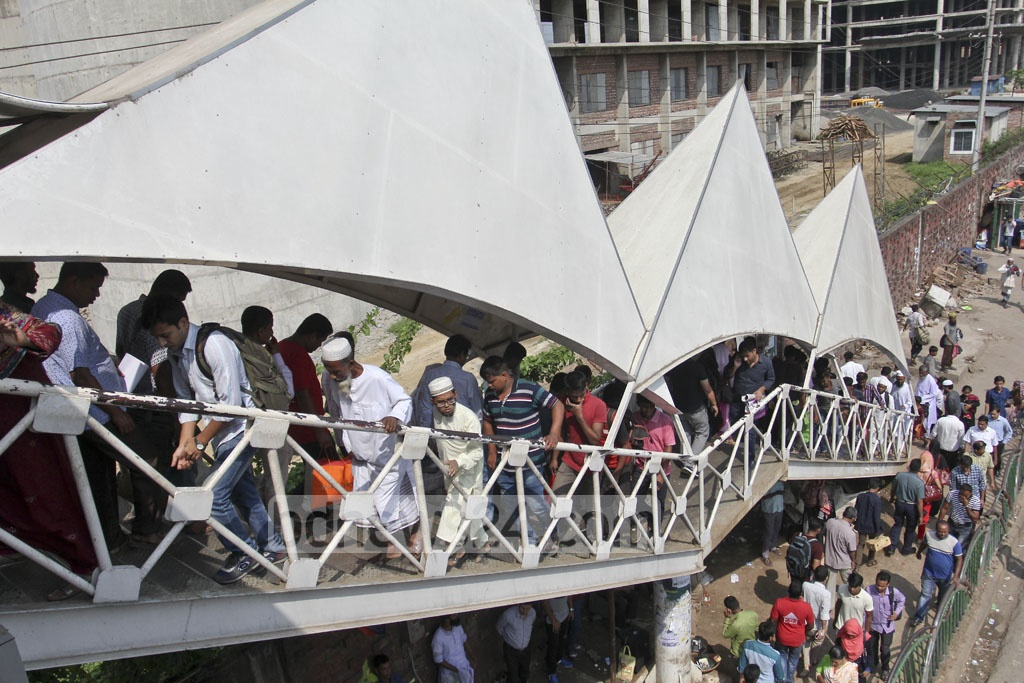 The footover bridge near Hazrat Shahjalal International Airport becomes crammed with people as the escalator on one side of it has been out of operation over the last 15 days. The photo was taken on Thursday. Photo: asif mahmud ove