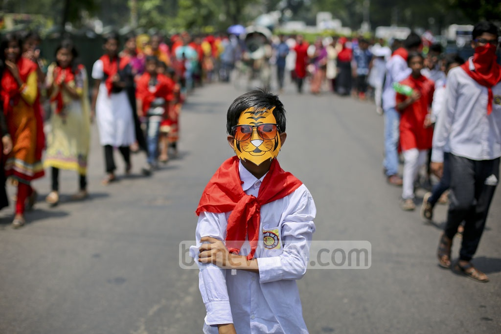 Children donne masks and carry displays for Khelaghar's parade on Friday. Photo: asaduzzaman pramanik