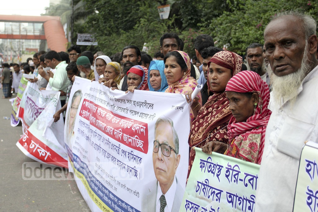 People from Mithamoin Upazila in Kishoreganj, now residing in Dhaka, urge the government to declare a national crisis in haor areas, during a demonstration in front of the National Press Club on Saturday.