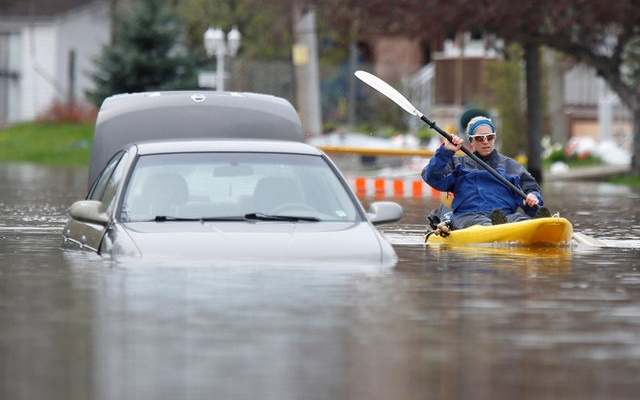 A woman paddles a kayak past an abandoned car on a flooded residential street in Gatineau, Quebec, Canada, May 4, 2017. Reuters