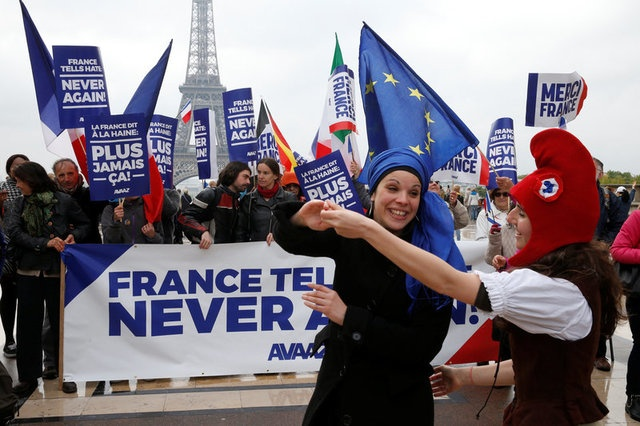 People gather with French and European flags near the Eiffel Tower with a banner with the message,